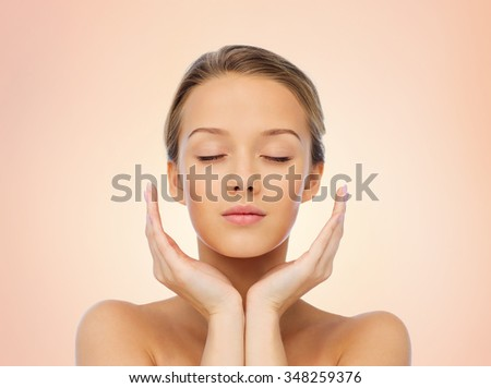 beauty, people, skincare and health concept - young woman face and hands over beige background - stock photo