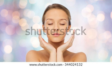 beauty, people, skincare and health concept - young woman face and hands over purple holidays lights background - stock photo
