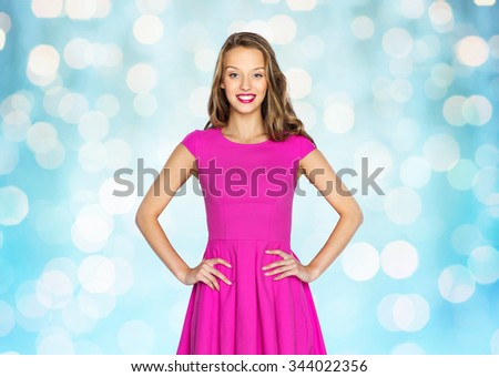 beauty, people, style, holidays and fashion concept - happy young woman or teen girl in pink dress over blue holidays lights background - stock photo