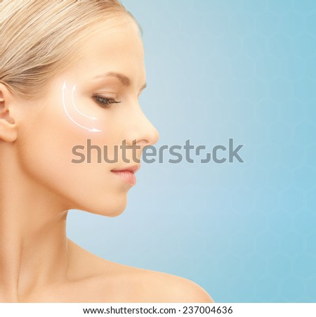 beauty, plastic surgery, aging, people and health concept - beautiful young woman face with lifting arrows over blue background - stock photo