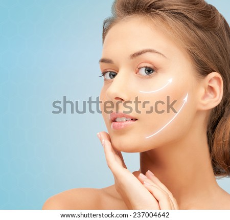 beauty, plastic surgery, aging, people and health concept - beautiful young woman touching her face with lifting arrows over blue background - stock photo