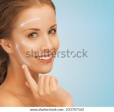 beauty, plastic surgery, anti-aging, people and health concept - beautiful young woman applying creme to her face with lifting arrows over blue background