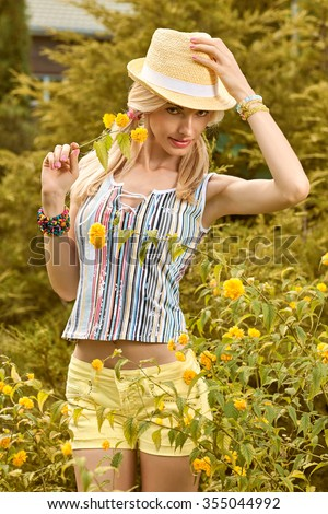 Beauty playful woman relax in summer garden dreaming, outdoors. Attractive happy blonde girl in hat with flower enjoying nature, lifestyle.   - stock photo