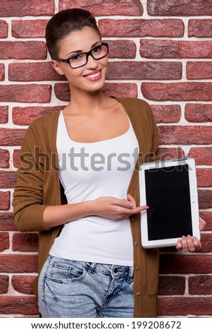 Beauty pointing copy space. Attractive young short hair woman in glasses holding digital tablet and pointing it while standing against brick wall - stock photo