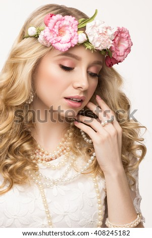 Beauty portrait. Beautiful blonde girl with wreath of flowers. Looking down. Playing with pearl necklace. Isolated on white background - stock photo