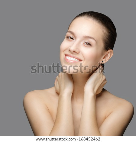 Beauty Portrait. Beautiful Woman Touching her Face. Perfect Fresh Skin. Isolated on Grey Background. Pure Beauty Model. Youth and Skin Care Concept. Nude make-up. - stock photo