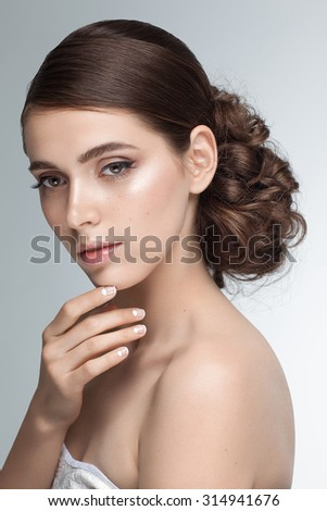 Beauty portrait closeup of young beautiful attractive model posing in studio looking at camera. Shiny brown hair, nude natural makeup, moon manicure. - stock photo