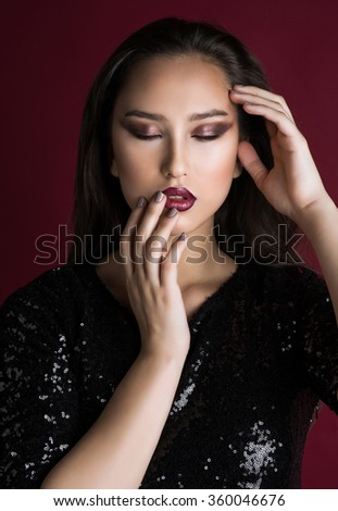 Beauty portrait of a beautiful feminine Asian brunette  with long hair in a black sequined dress with red lips and smoky eyes with eyes closed in the studio on a red background holding hands at head - stock photo
