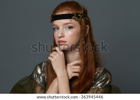 Beauty portrait of a charming woman in fashion cloth looking at camera over gray background - stock photo
