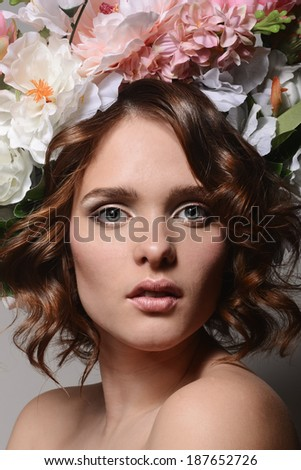 Beauty portrait of a girl with flowers in her hair on a gray background - stock photo