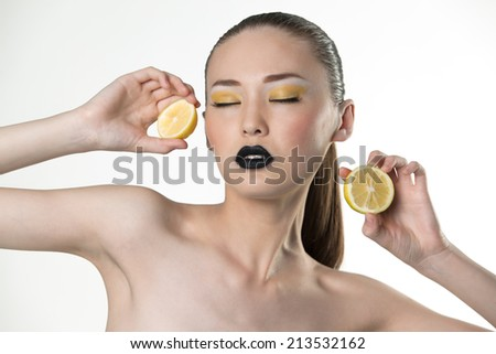 Beauty portrait of a girl with lemon on a white background