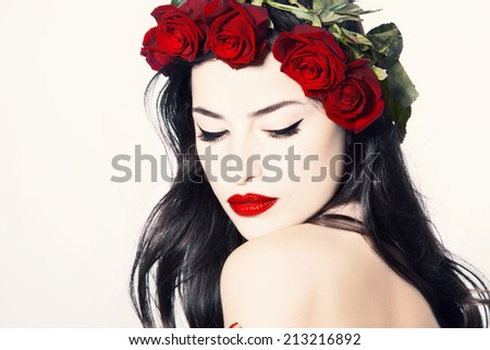 beauty portrait of a gorgeous woman with wreath of red roses on her head, studio white - stock photo