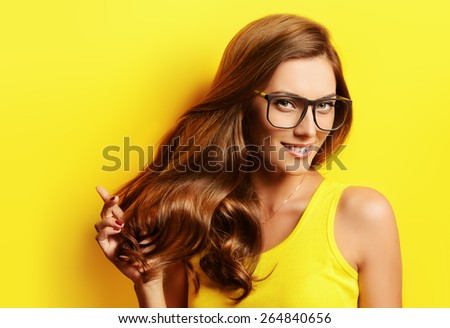 Beauty portrait of a happy young woman in spectacles and bright yellow dress over yellow background. Beauty, fashion. Optics. - stock photo