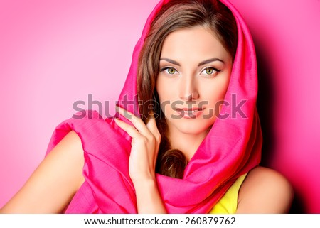 Beauty portrait of a positive young woman in bright crimson headscarf over pink background. Beauty, fashion. Cosmetics.  - stock photo