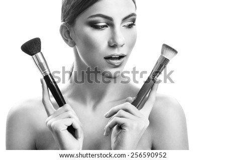 Beauty portrait of a woman on a white background with a brush, black and white