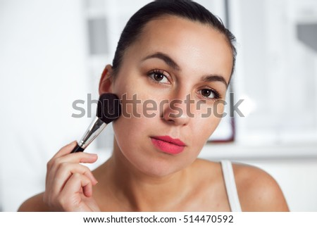 Beauty portrait of a woman with a brush.Makeup artist applying blusher