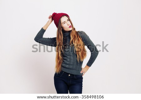 Beauty portrait of a young beautiful girl with long ombre straight hair wearing marsala color warm hat. Magnificent hair. Lips care. Young blonde hipster girl having fun and sending you and kiss  - stock photo