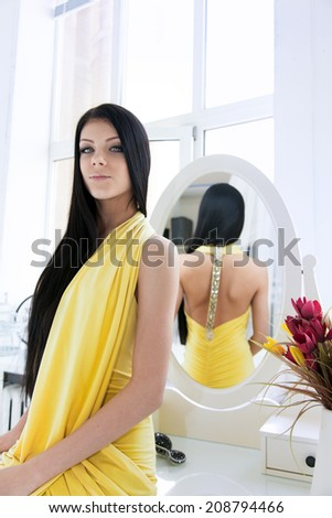 Beauty portrait of a young brunette woman in bedroom. - stock photo