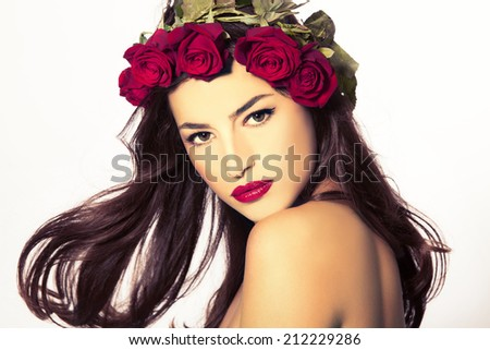 beauty portrait of a young woman with a wreath of red roses on her head - stock photo