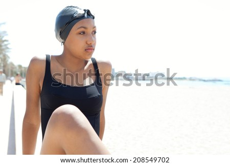 Beauty portrait of an athletic focused african american teenager swimmer wearing goggles and swimwear relaxing on a white sand beach with a sunny sky. Summer sport and lifestyle.