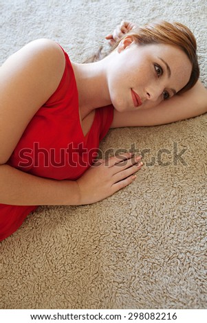 Beauty portrait of an attractive young woman laying on a bed at home wearing a bright red dress and gently smiling, looking away thoughtful, home bedroom interior. Beauty feminine indoors lifestyle. - stock photo