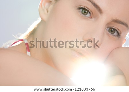 Beauty portrait of an attractive young woman looking at the camera with direct sun light filtering through her face with perfect skin. - stock photo