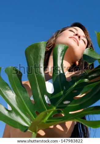 Beauty portrait of an attractive young woman wearing a bikini standing next to exotic green leaves against an intense blue sky during a sunny day, outdoors. - stock photo