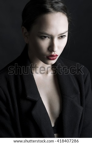 Beauty portrait of asian girl with red lips in black coat - stock photo