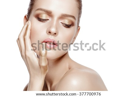 Beauty portrait of attractive model with brunette hair. Fresh, clean skin.  Professional makeup. Tender colors. Gold hands. Closed eyes. White background, isolated. - stock photo