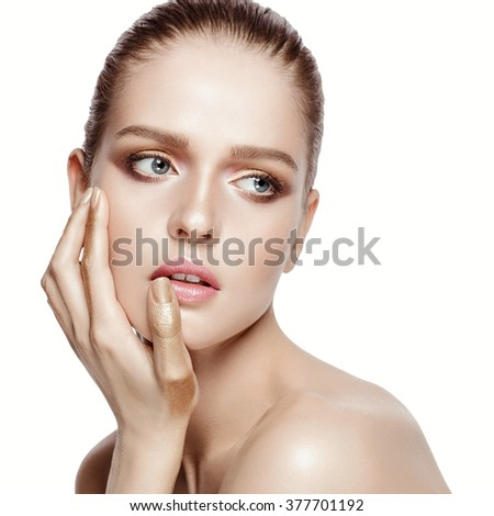 Beauty portrait of attractive model with professional makeup. Blue eyes, brunette hair. Fresh, clean skin. Tender colors. Gold hands. White background, isolated.  - stock photo