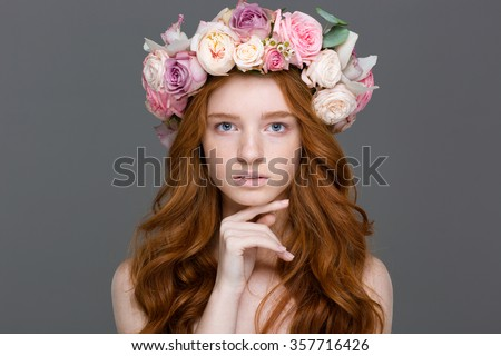 Beauty portrait of attractive young woman with curly red hair in flower wreath over grey background - stock photo