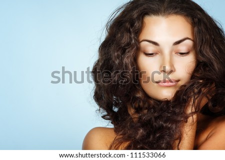 Beauty portrait of beautiful cheerful young fresh woman with long brown healthy curly hair. Isolated on blue background - stock photo