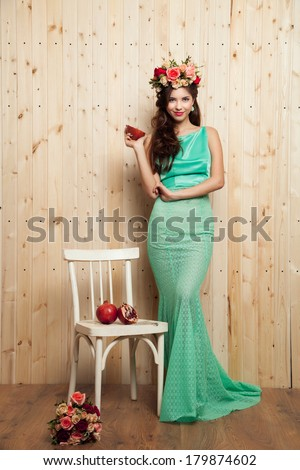 Beauty portrait of cheerful woman with flower wreath and pomegranate on wood background