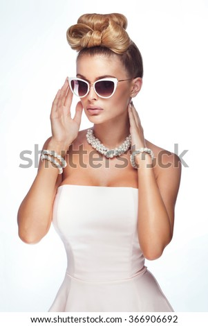 Beauty portrait of elegant attractive blonde woman wearing pearls and stylish sunglasses. Fashionable hairstyle.