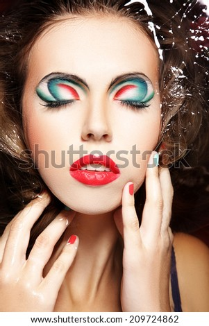 Beauty portrait of fashion model with colorful waterproof makeup in water