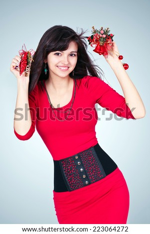Beauty portrait of gorgeous attractive young girl like santa in red costume with alluring christmas vivid presents hanging and sexy thin waist with black belt in new year eve isolated over studio room - stock photo