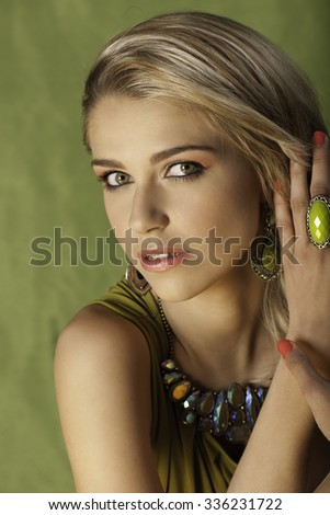 Beauty portrait of lovely blonde woman with natural makeup and bright orange nail polish in front of green background - stock photo
