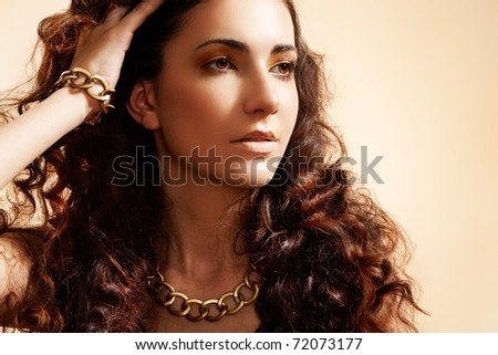 Beauty portrait of luxury fashion woman with glamour gold jewellery, curly hairstyle  on beige background. Accessories and jewelry.
