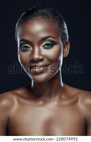 Beauty portrait of smiling handsome ethnic african girl, on dark background - stock photo