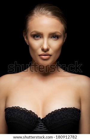 Beauty portrait of stunning young female model wearing black underwear. Blue eyes and blond hair. - stock photo