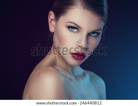 Beauty portrait of stylish female with professional makeup and retro red lips. Young lovely Caucasian fashion model posing with naked shoulders over dark background.   - stock photo