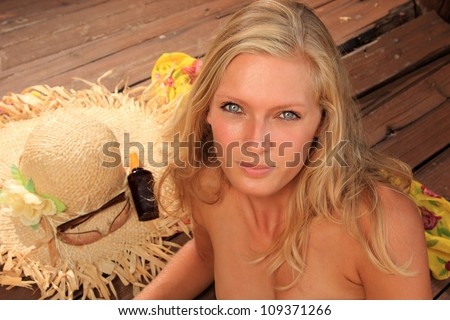 Beauty portrait of woman laying on wooden floor with straw hat sunglasses and suntan oil