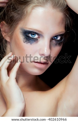 Beauty portrait of woman with black messed make up on black background in studio