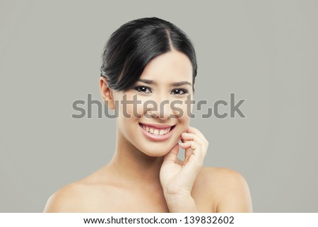 Beauty portrait of young asian woman with a beautiful smile, over a gray background - stock photo