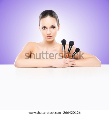 Beauty portrait of young, attractive, fresh, healthy and natural woman with a makeup brushes and a blank billboard - stock photo
