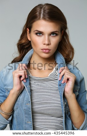 Beauty portrait of young attractive haired woman, isolated on gray background