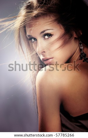 beauty portrait of young brunette woman, hair fly, studio shot - stock photo
