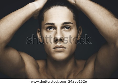 Beauty portrait of young handsome man against blue background - stock photo