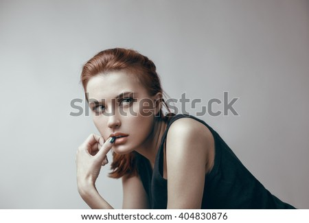 Beauty portrait of young pretty red-haired dreaming girl with long straight hair. Beautiful makeup. - stock photo