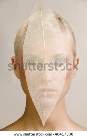 beauty portrait of young woman covering her face with a transparent leaf - stock photo